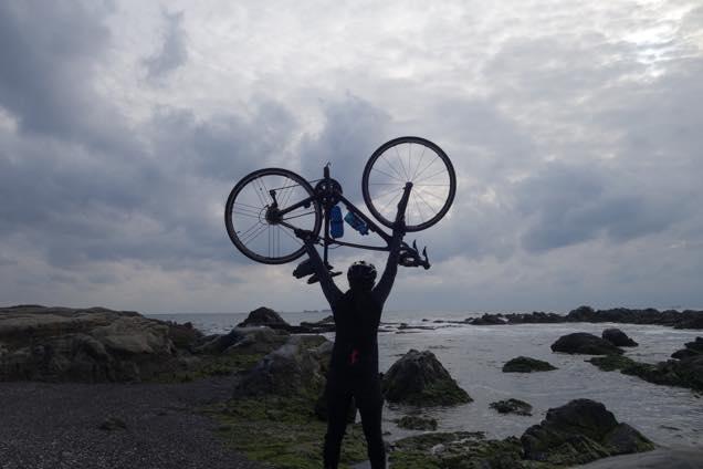海を背景にロードバイクを持ち上げて自撮りする筆者