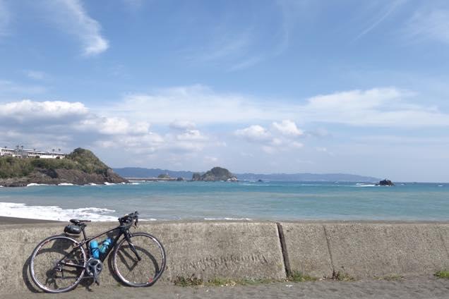 青空と穏やかな波打ち際にロードバイクを止めています