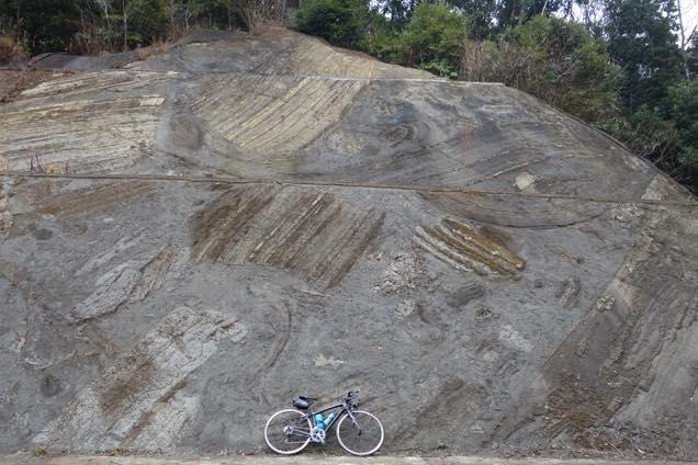 海底の地すべりの後がギザギザに残る大きな岩にロードバイクを立てかける