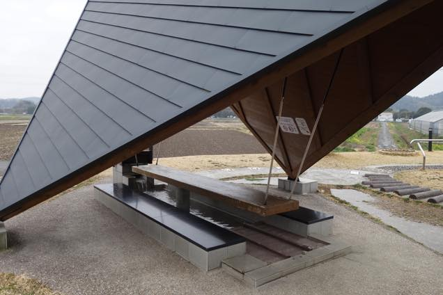 田んぼに囲まれ、大きな屋根のついた道の駅三芳村のベンチ