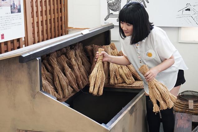 納豆室で藁を持つ朝井さん
