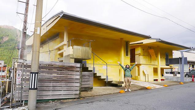黄色い外観の早稲田桟敷湯の前でポーズをとる筆者