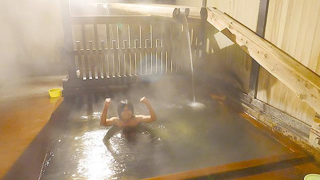 滝の湯の湯船につかってガッツポーズする筆者