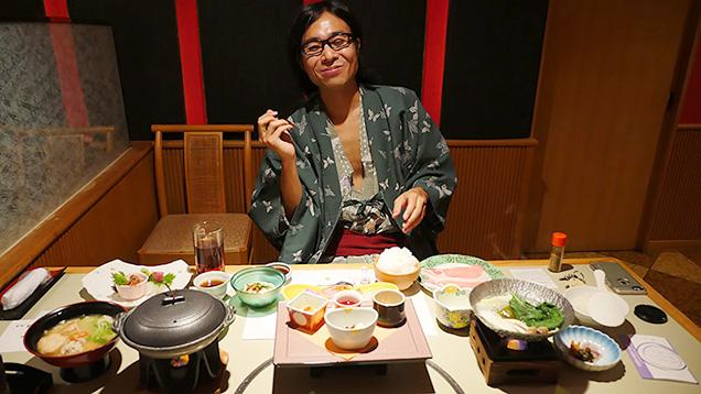豪華な料理の前で笑顔の筆者