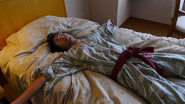 ホテルのベッドで眠る筆者