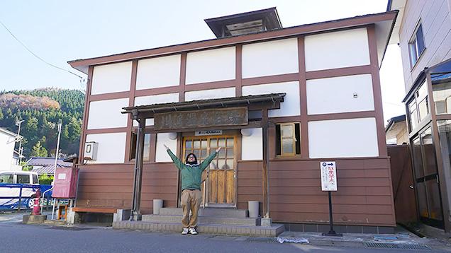 川渡温泉浴場の入り口でポーズをとる筆者