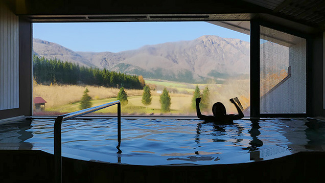 青空と山が見えるホテルオニコウベの温泉につかり、ガッツポーズする筆者