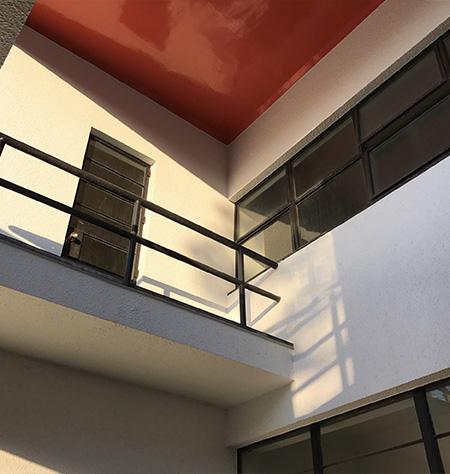 黒い鉄柵や窓枠、赤く塗られたバルコニーの天井