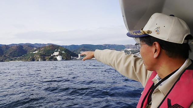 船に乗り向こうの島を指さす西海尊志さん