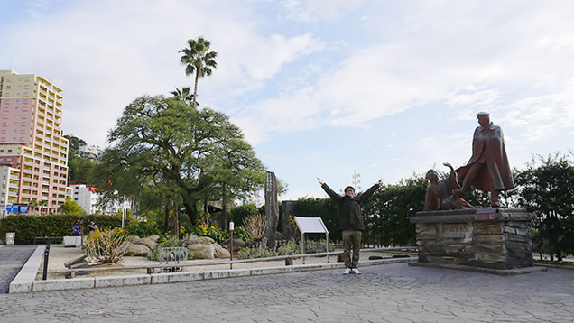 お宮の松と近くの銅像の間に立ちポーズを決めるライター地主恵亮