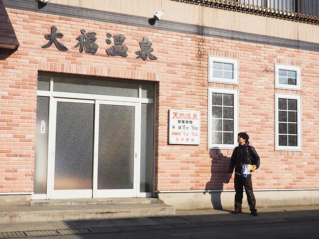 青森駅から車で15分の銭湯「大福温泉」の前に立つ毎川直也