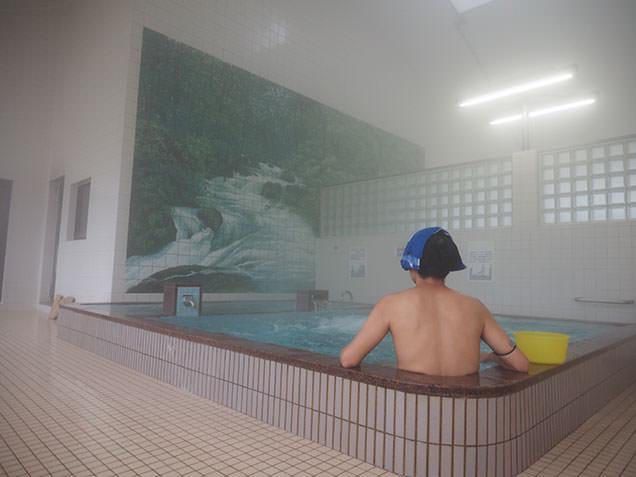 徳乃湯温泉で入浴し十和田湖の背景画を眺める毎川直也