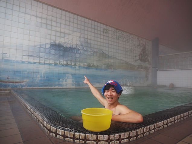 出町温泉の富士山の背景画を前に入浴する毎川直也