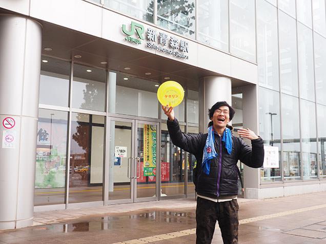 JR新青森駅前で風呂桶を掲げる風呂デューサー毎川直也