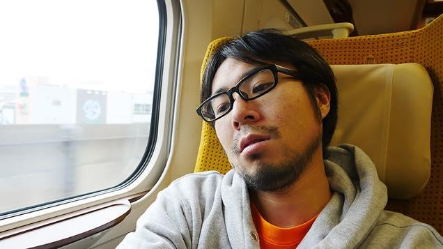 新幹線こまちの座席で疲れた表情を見せる筆者