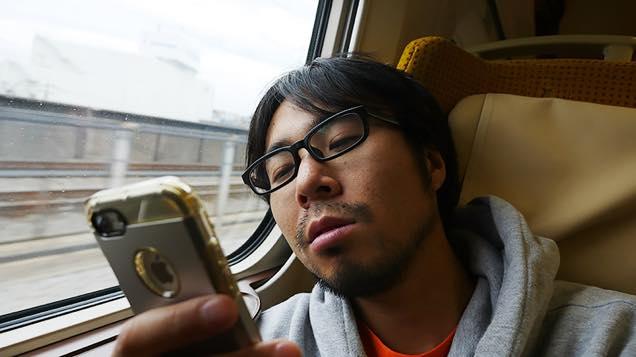 新幹線の座席で疲れた表情でスマホを眺める筆者