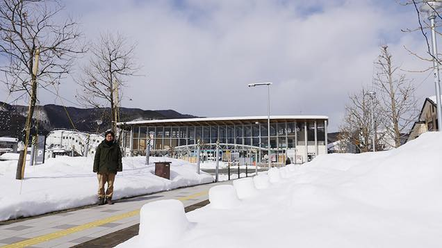 雪に囲まれた田沢湖駅前に立つ筆者