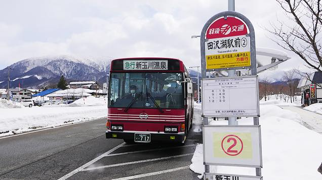 新玉川温泉行きの赤い急行バスがバス停に到着