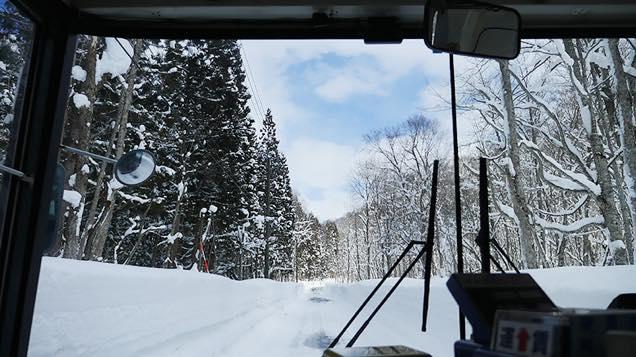 雪が積もった山道を進むバス