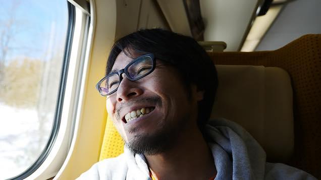 新幹線の座席で元気な笑顔を見せる筆者