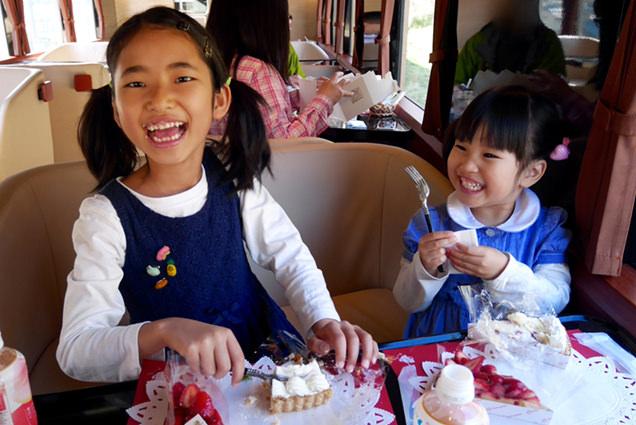 いちごのケーキを食べて満面の笑みを浮かべる姉妹