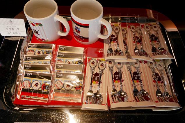フルーティアふくしまオリジナルグッズのマグカップや缶バッヂ、スプーンとフォームのセットが並ぶ