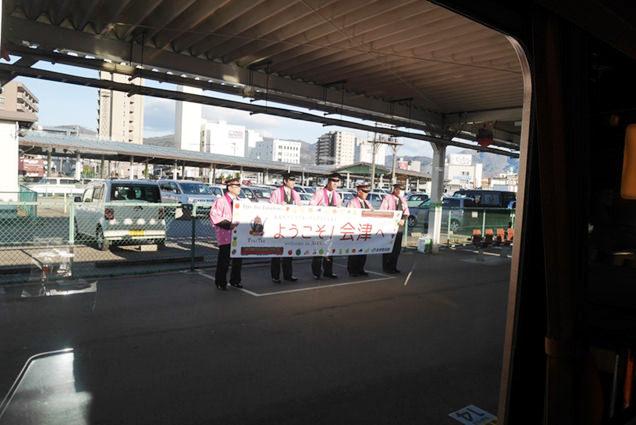 会津若松駅ホームで「ようこそ会津へ」の旗を持った駅員さんが並んでいる