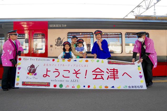 フルーティアふくしまの列車の前で、駅員さんの帽子をかぶり記念撮影をする家族