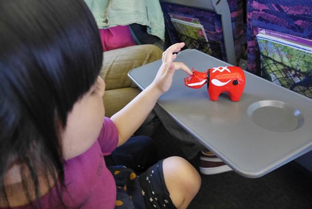 新幹線のシートでおみやげの赤べこを眺める次女