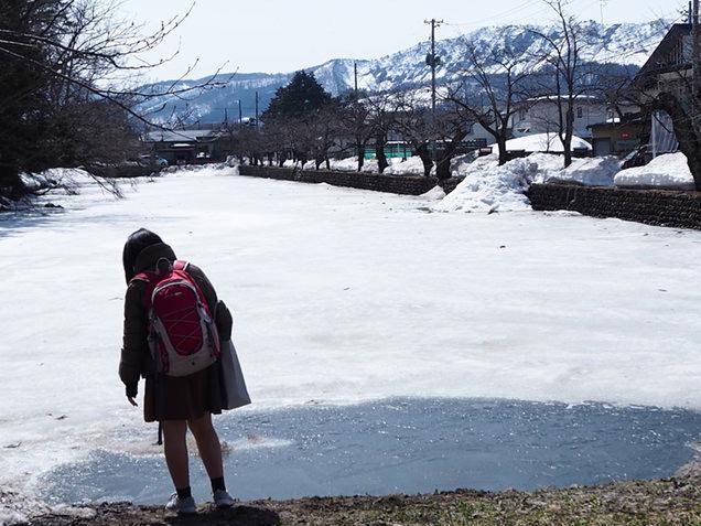 米沢城址の凍ったお堀の前に立つ娘