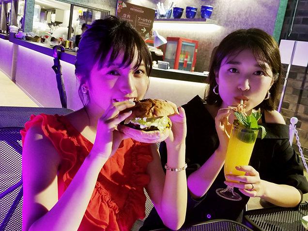 ハンバーガーをほおばる女性2人