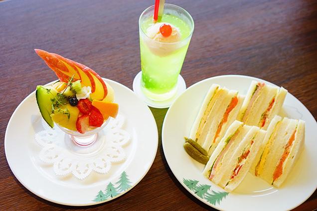 カフェのサンドウィッチとフルーツパフェとクリームソーダ