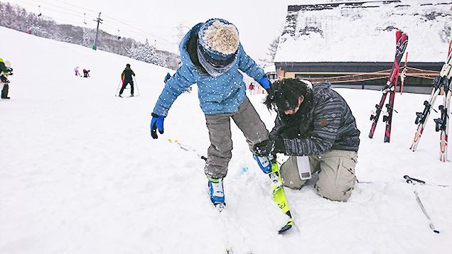 子どもにスキーを履かせる筆者