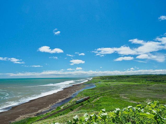 根室本線尺別駅近く、原野を走る列車と海岸が同時に望める「尺別の丘」で撮影された一枚。