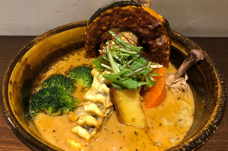 スープの中にキャベツ、サツマイモ、ピーマンなどがかくれんぼ