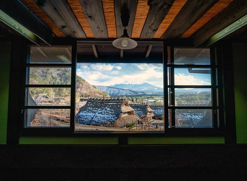 茅葺き屋根の家屋内からの富士山